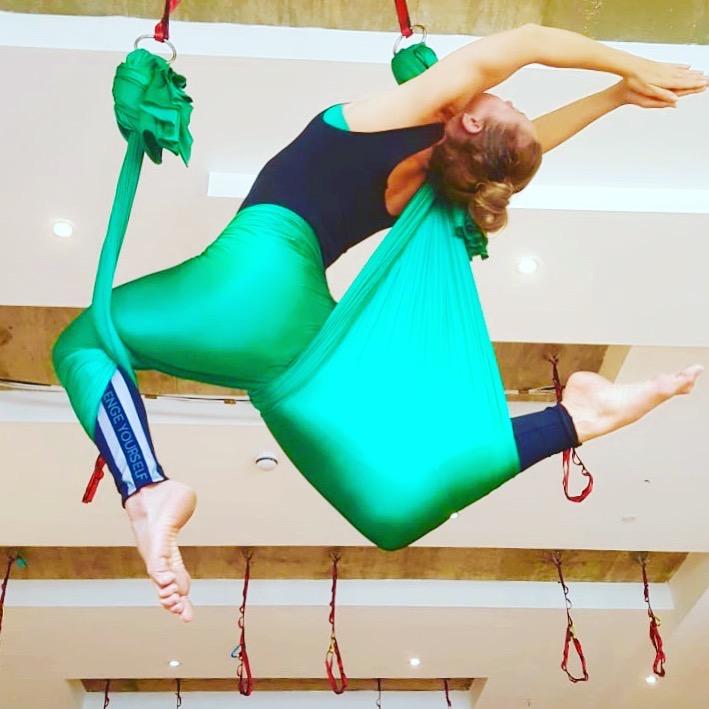 Aerial yoga pose using silks